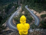 Man in a yellow jacket looking down on a road from a hillside.