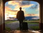 A man with a suitcase looks through an arch at a cloudy sunset.