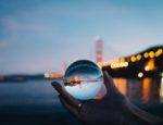 A hand holding a clear glass ball in front of a body of water.