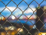 Looking through a chain-link fence at a city skyline.