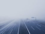 A foggy highway with cars driving into mist.