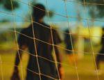 Looking at a goalie through a soccer goal's net.