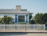 White and blue house behind white picket fence.