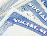 Several Social Security cards laying on top of each other.