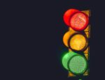 A traffic light with red, yellow and green lights illuminated.
