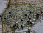 A paper map of the United States with pins on its cities.