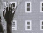A hand on a window facing outside.