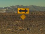 A bidrectional arrow road sign in the California desert.