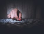 A person picking up a small jigsaw puzzle piece.