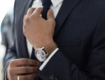 Man in a business suit straightening his tie.
