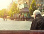 A senior man sitting alone on a bench.