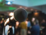 A microphone on a stand in front of a crowd.