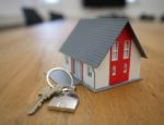 Miniature house sitting on a table next to a house key.