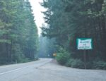 A sign reading 'Welcome to Oregon' on the side of a road between pine trees.