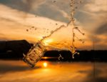 A glass of water splashing out in front of a sunset.