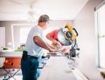 A man working inside a home in front of a table saw.