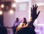 A person raising their hand in a meeting.