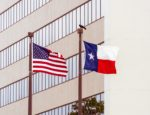 The flags of the United States and the state of Texas flying side by side in daytime.