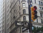 The street signs at the intersection of Wall Street and Broadway in New York City.