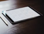 A calendar displayed on an iPad, sitting on a table.