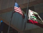 The flags of the United States and the state of California flying side-by-side.