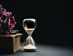 An hourglass sitting beside a book.