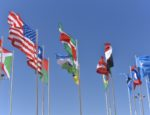 Various world flags on the tops of flagpoles during the day.