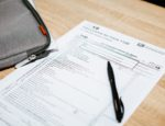 An IRS tax form sitting on a table, with a pen placed on top of it.