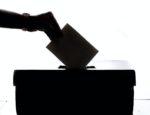 A hand placing a ballot in a box.