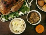 Close-up of a Thanksgiving dinner with turkey, mashed potatoes and bread rolls.