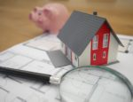 A magnifying glass on a paper next to a small model of a house and a piggy bank.