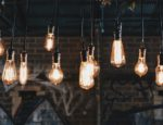 A group of vintage lightbulbs illuminated and hanging from a ceiling.